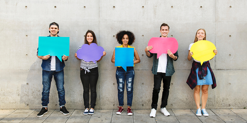 Five students holding cut outs of speech and thought bubbles