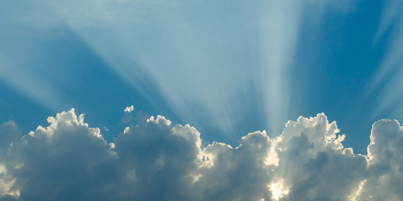 Blue sky and sun rays showing through clouds